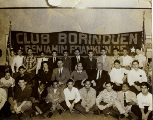 "A black and white photograph of a group of students in front of a banner reading ""Club Borinquen Benjamin Franklin HS"""