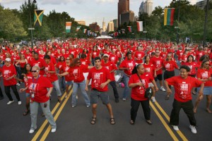 a color photograph of a parade of people wearing red tee shirts dancingdown the Benjamin Franklin Parkway