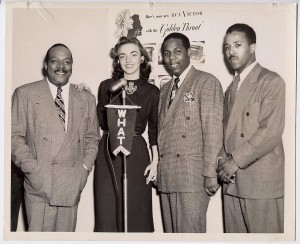 Black and white photograph depicting Jazz legend Count Basie with members of the WHAT staff.