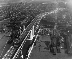 An aerial photograph of the newly completed Benjamin Franklin Bridge in 1926, and the surronding neighborhoods in Camden.