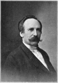 A black and white photograph of inaugural conductor Fritz Scheel, in formal attire with slicked hair and large, characteristic, curly mustache.