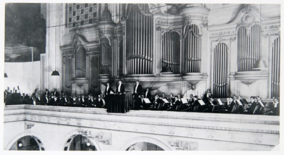 A black and white photograph of the Philadelphia Orchestra (and all members in formal attire) on the second level of the Wannamaker Store's Grand Court; behind them, Wannamaker's Great Organ.