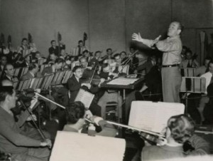 A black and white photograph of Eugene Ormandy conducting the Philadelphia Orchestra at rehearsal with arms eccentrically outstretched.