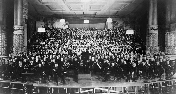 A black and white photograph of the Philadelphia Orchestra on stage at the Academy of Music