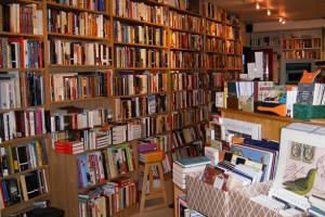 An image of the interior of Joseph Fox Bookshop featuring a wall covered in bookshelves and colorful books, with the front desk on the right-hand side (featuring more books).