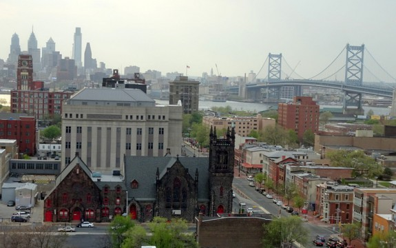 photograph of Camden in foreground with Ben Franklin Bridge and Rutgers-Camden campus at right and Philadelphia skyline rising in distance across Delaware River