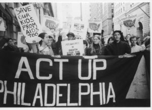 A black and white photograph of HIV/AIDS activists from ACT-UP Philadelphia marching with signs