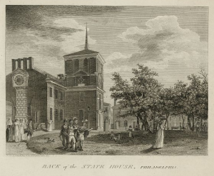 A print of an etching of the Philadelphia State House (or Independence Hall) from the rear, with a group of Native Americans standing in front on the grass and a group of high-class Philadelphians walking on a path from the State House on the far left.  Trees stand in a park to the right, and near the center of the composition, Peale's Museum can be seen in the background beyond several people lounging on the grass beside the State House.