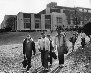 Black and white photograph depicting several young men walking away from a large school building.