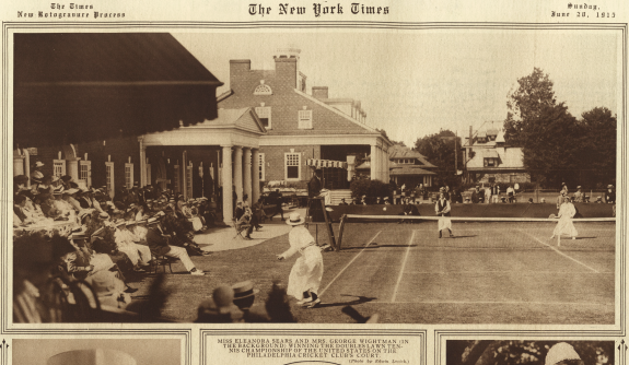 An image from the New York Times published in July 1915 of a women's doubles tennis match taken from behind the court, picturing the clubhouse and its columns to the left, along with a group of spectators under an awning.