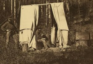 A photograph of an observatory tent with a man operating a theodolite.