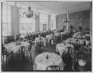 A black and white photograph of the interior of the Philadelphia Country Club dining room with windows along the left wall, two chandeliers and neatly-set tables arranged around the room.