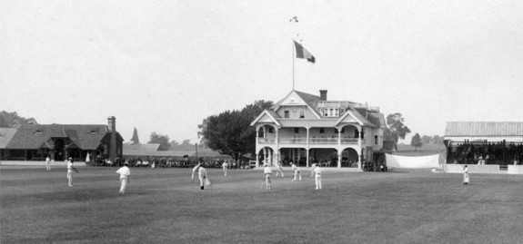A black and white photograph of the Philadelphia Cricket Club's three-story clubhouse, with grounds in the foregrounds featuring members playing a game of cricket. A large banner is strung up to the right of the clubhouse and a crowd can be seen in the distance between the clubhouse and a steep-roofed house at the left edge of the frame.