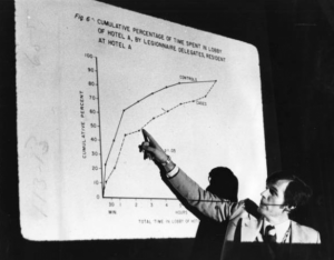 A black and white photograph of a man at a Legionnaire's symposium pointing to a graph about the epidemic