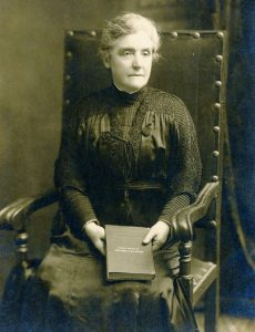 Black and white photograph of a woman seated in wooden arm chair holding a book.