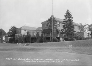 A black and white photograph of the Torresdale-Frankford Country Club clubhouse from a 45 degree angle, viewed from the golf greens.  Several trees and shrubbery trim the two-story buildings perimeter.