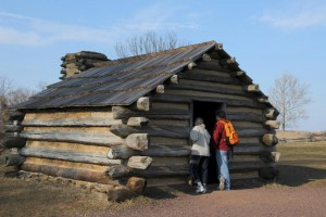 Color photograph of a log cabin or hut.