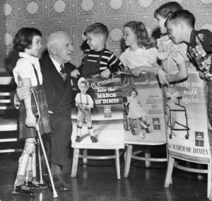 a black and white photograph of five polio stricken children holding March of Dimes posters with Philadelphia March of Dimes leader