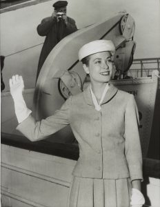 A black and white photograph of Grace Kelly waving