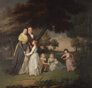 A painting of James Peale and his family, seemingly walking in a park, or at least, through a wooded area near a river (visible at right, near the horizon). He wears a red coat with brass buttons and a white scarf, and walks arm-in-arm beside his wife, Mary Claypoole, who wears a blue and white dress with a yellow shawl wrapped around her body. Four children are also present in the painting. The oldest girl, in a white dress, faces her mother and holds her hand, while a girl in a pink dress (right) dances, and two children, a boy and a girl, sit on the ground (center). The girl holds an infant and the boy wears a black top hat and is holding an apple. A large, leaning, red-leafed tree is directly behind them, with small plants and foliage in the foreground. A cloudy blue sky can be seen in the distance.