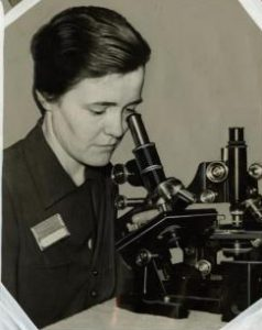a black and white photograph of Dr. Ruth Patrick looking through a microscope