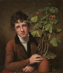 A portrait of Raphaelle's brother, Rubens Peale, seated at a wooden table, head angled slightly, with his hand around the clay pot of a large, green geranium plant with thick stalks and small red flowers. Rubens holds a pair of glasses on the table with his other hand, while wearing a pair of smaller diameter spectacles midway up his nose. He wears a reddish-brown coat and white scarf and undershirt. His hair is brown and the background is a slightly amber tannish-brown tone.