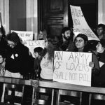 Black and white photograph of demonstrators holding signs.