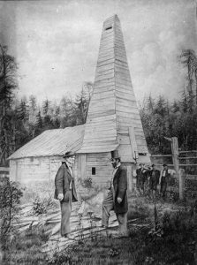 Black and white photograph of two men standing in front of the first oil well. Three men lean against a fence in the background.