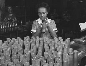 Photograph of a young African American woman inspecting artillery shells, in the background other young women can be seen doing the same task.