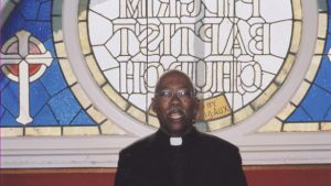 A color photograph of Baba Abiodun in clerical dress in front of a stained glass window