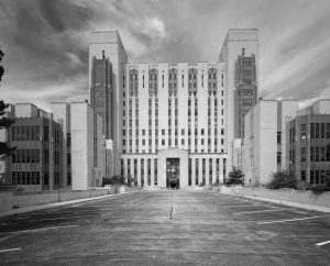 Black and white photograph of the Naval Hospital main building, a multi-story building with an ornate art deco design. perspective is from the street, about 50 feet away from the entrance