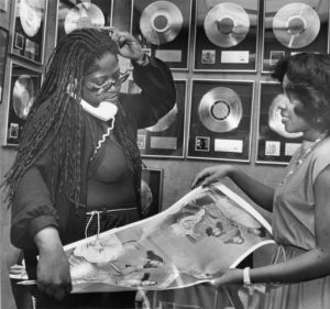 Black and white photograph of two women looking at photos of recording artists, several gold or platinum records hang on the wall behind.