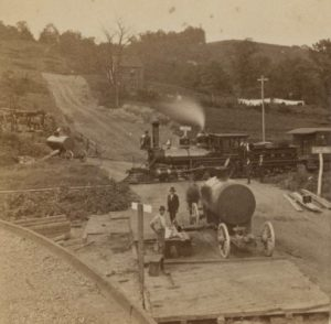 Sepia-toned photograph of two men using a horse-drawn wagon to transport an oil tank while a train passes in front of them.