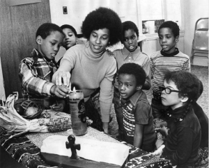 A black and white photograph of a teacher and a group of children lighting a candle with other Kwanzaa symbols around