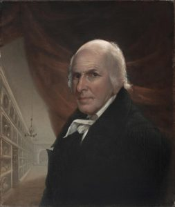 A self-portrait painting by Charles Willson Peale. He stands (depicted bust-up) in front of a red curtain with a hallways behind him to the left. Shelves line the hallway wall, filled with various implied antiques. A delicate chandelier hands about halfway down the hallway above an open door to the left amongst the shelving. Peale is bald on top with brown eyes,wearing a black overcoat over a white-collared shirt.