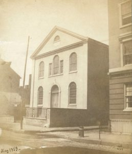 Sepia-toned photograph of the front of the two-story church building with arched windows and an arched doorway.