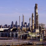 Full color photograph of oil refineries, center city can be seen in the background.