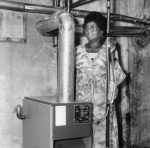 A woman stands next to her home heating system that is fueled by gas