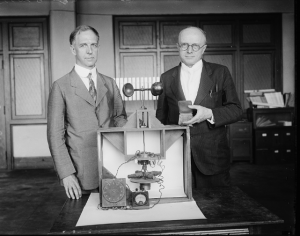 A black and white photo of Paul R. Heyl and Lyman James Briggs with their earth inductor compass and the magellanic premium award