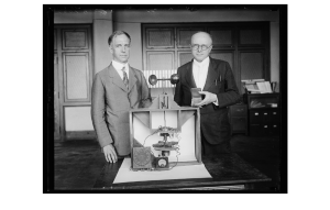 A black and white photograph of Paul Heyl and Lyman Briggs with their earth inductor compass and the Magellanic Premium award