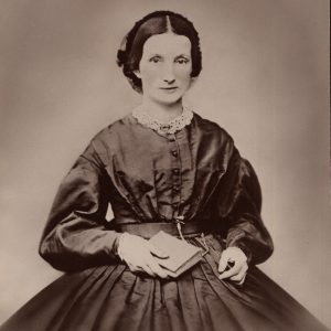 Black and White photograph of a women in a nineteenth-century dress holding a book in her right hand.