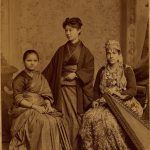 Nineteenth century sepia-toned photograph of three Asian women wearing traditional dress of their respective nations: India, Japan, and Syria.