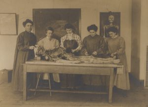Nineteenth century sepia-toned photograph of five women dissecting a human cadaver.