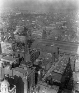 Black and white photograph overlooking Thirteenth Street with the Hotel Vendig in the foreground and the old Reading Terminal right center. The Delaware River is visible in the distance.