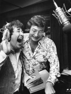 Hy Lit (left) with his hand raised and mouth open, laughing, wearing a denim vest over a white, pocketed, collared shirt with a headset on. Joe Niagara is to his right (center) holding a stack of 45rpm records and wearing large glasses and a jumping-horse-patterned collared shirt. A microphone on a boom arm is on the right.