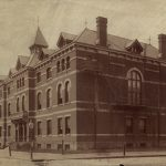 Sepia-toned photograph of a large, three story building.