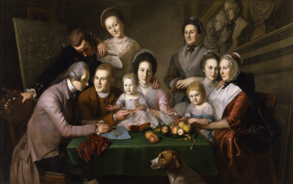 An image depicting Charles Willson Peale's family and children seated around a table, some standing, others seated. A peeled apple sits symbolically on a plate near the front of the table. His brothers work on a drawing of his mother, seated opposite them, several busts are located on a shelf at the top right, and a painting of the three maidens is to the left.