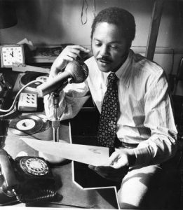 George Woods sits facing left, but toward the camera. He holds a sheet of paper up with the top near the camera, likely reading something on air into the large microphone that sits in front of him on a short stand. A rotary phone is near the front of the frame and a small clock is in the background. Two 45rpm records lay in front of him next to a small two-position switchboard. He has short hair, sideburns and a mustache, and wears a stripes, light-colored or white shirt with a patterned dark tie.