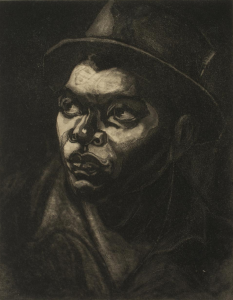 A dramatic portrait (carborundum print) of a man wearing a hat, looking upward and to the left, with light shining on his face from that direction. He wears a collared shirt and the background is pitch black, with light accents around the edges of his hat.