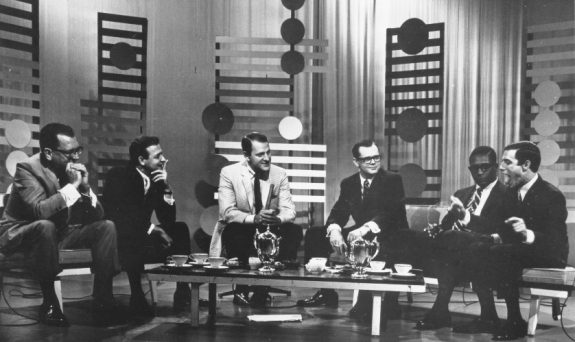 six men sit around a coffee table (with coffee cups and a chromed kettle atop it), all leaning forward in discussion, presumably, about music. the backdrop of the set is decorated with standing wooden slats, like vertical fences and modernist circles. The men all wear suits and ties, most smirking, looking toward Jerry Blavat (far right), who has his arms outstretched and is sticking out his tongue.